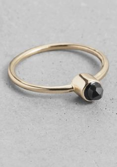 This subtle ring is crafted from gilded brass and is topped with a tiny faceted gemstone.