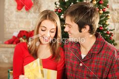 Young couple exchanging Christmas gifts    www.istockphoto.com/dszc