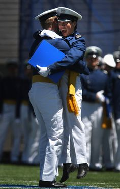 Air Force Academy graduates embrace after receiving their diplomas at the U.S. Air Force Academy graduation ceremony at Falcon Stadium in Colorado Springs, Colorado.