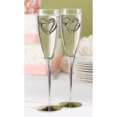 Sparkling Heart Flutes Nickel-plated stems with band of hearts at base of glass bowls. Rhinestone-studded, linked hearts charm on each bowl. Ideal glasses for the bride and groom to toast the start of the marriage with.