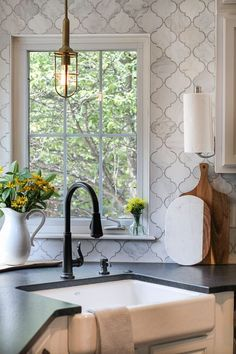 marble arabesque tile to the ceiling around windows and a corner sink in the kitchen.