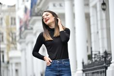 Anisa Sojka styles brown animal print leopard Moda in Pelle ankle boots | Black H&M roll neck top | Blue denim high-waisted mom jeans | Black quilted Chanel handbag with gold chain | Straight hair and red lipstick | Fashion blogger street style shot in London by David Nyanzi