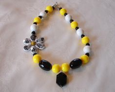 Add a touch of sunshine to her life with this cheerful yellow and black beaded necklace with a flower on the side and a black drop pendant. Measures approximately 17 inches and has a toggle closure.