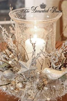 1920's style ornaments, twigs, feathers,  around a glass vase with candle placed on a plate.