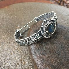 Dies ist ein wunderschön komplizierten Draht-Wickelarmband, die ich sorgfältig für reine Schönheit mit Komfort und Leichtigkeit erstellt. Ich begann mit stark aber flüssig beweglich 16 Gauge und 20 gauge Sterling Silberdraht. Magie ist durch diese schöne Labradorit und Opal Armband