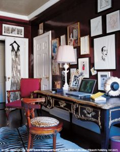 from elle decor...crazy about the raisin-colored walls in this study - the perfect backdrop for the salon-style art hanging and looks  fresh with the black and gold writing desk and the animal print fabrics.