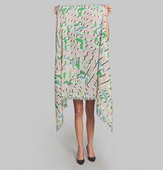 Foulard en laine, design Cadis, motif graphique asymétrique, teintes roses, vertes, bleues, noires et écrues, 2 bords francs.     Voyant ses créations comme la
