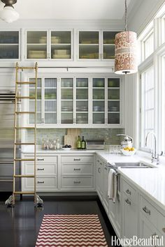 ROLLING LADDER – Adding extra storage up top is a great idea, if you can reach, that is. Katie Ridder installed a rolling ladder (just like the library!) in this fantastic kitchen to access ceiling-height cabinets. Click for more small kitchen ideas.