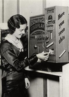 Cigarette vending machine in England delivered a lit cigarette for a penny, 1931
