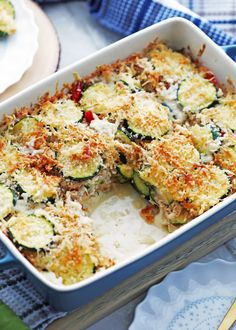 Zucchini Gratin that's topped with Gruyère and Panko Breadcrumbs in a blue casserole dish. One piece is removed.