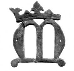 Religious badge or mount in the form a crowned lombardic 'M'. The 'M' is for MARIA and with the crown signifies Our Lady, the Virgin Mary as Queen of Heaven.