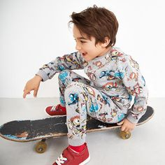 Boy in monster-print sweatshirt and jogging bottoms with skateboard