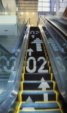 Ø3 [Wayfinding Escalator] / By Hiromura Masaaki_This unconventional yet innovative idea of using the movement of the escalator to create an illusion of the arrows moving puts the use of the working environment to the test. [not only it looks good, but it makes sense.]