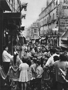 La foule habituelle de la rue Mouffetard, fin années 1950. Un vendeur offre des marchandises qui semblent particulièrement intéresser les enfants...  (Paris 5e)