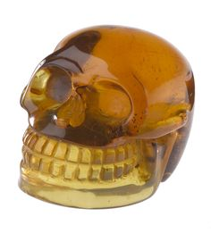 Amber, yellow-brown, carved and polished in the form of a skull, containing several small inclusions, from La Pimienta Mine, near Simojovel, Chiapas, Southern Mexico.