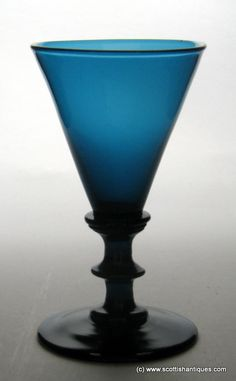 Peacock Blue Regency wine glass c1820 Bowl : Conical Stem : Annular knop above a central angular knop Foot : Conical Pontil : Snapped Peacock blue is a rare Regency glass colour. Superb example with a lovely hue http://scottishantiques.com/georgian-wine-glasses/regency-coloured?product_id=4104#.Vj8Fw6Toq-4