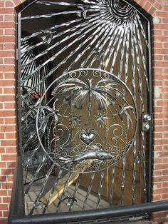 Tropical scene wrought iron door.
