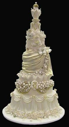 All-white, Victorian-style wedding cake that has multi-tiered, artful embellishments. Fondant draping, edible bubbles, sugar flowers; it has it all!