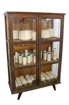 CRISTALEIRA PALITO - Cristaleira de madeira com pés palito e três prateleiras. Usada guardar bobinas de amostras de fios de tecelagem. Alt. 168,5 cm, Larg. 110 cm, Prof. 47,5 cm