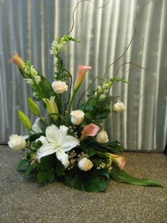 Casablanca lilies, pink calla lilies, white snap dragons, white roses with tropical greenery and curly willow
