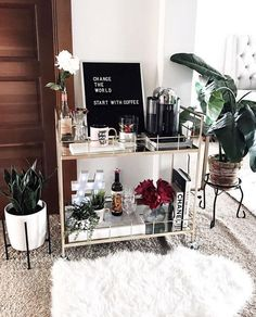 letter board, plants, and coffee table books on a bar cart