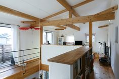 白牆+木樑 2階。天井板は張らず梁を見せたつくり。奥に見えるのが多目的スペース。