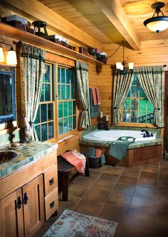 This spacious master bathroom is in the McKay Model Home by Hochstetler Log Homes. The McKay floor plan's master bathroom features a garden tub and shower, double vanity, linen closet, and walk-in closet. #loghome #logcabin #loghomebathrooom #exposedbeams