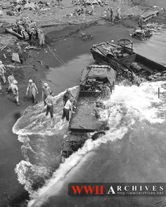 """World War II Photograph: The landings on Iwo Jima, brutally tough under heavy Japanese fire, were made even tougher for Coast Guard and Navy crews by the heavy, grinding surf, which wreaked havoc with many a landing craft.  Here, beach parties attempt to square away two """"ducks"""", battered by the combers and rapidly filling with water on the blackened sands of the volcanic island fortress."""