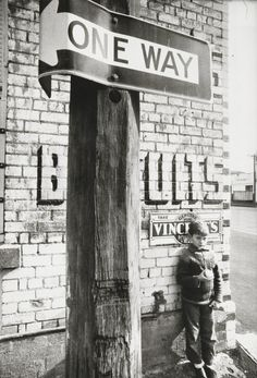 No title (Boy and one way street sign) | Mark STRIZIC. (from the Children of the streets series (c. 1970)