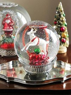 DIY Snow Globe Centerpieces : Snow globes are a Christmas classic, and these oversize spheres put on an impressive display. The glass globes are small flower aquariums with magnifying qualities that give the contents an added wow factor.