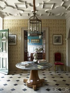 A 20th-century English lantern hangs above a 19th-century French center table in the hall; the wallpaper is custom-painted, and the flooring is reclaimed Burgundy stone.