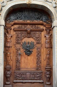 An old wooden door with ornaments and sculptures in old city..
