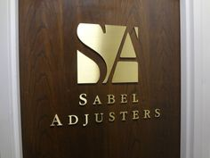 Custom precision cut-out dimensional brass metal letters pin mounted flush onto interior wooden door in NYC. For more information on brass business signs and lettering, visit http://www.SignsVisual.com