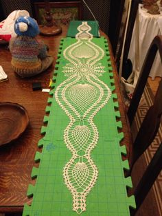 Crocheted Table runner I adapted to fit my dining table. Pinned out on crochet boards.
