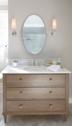 timber vanity, oval mirror, sconces