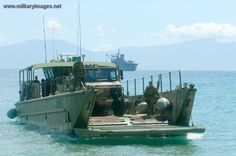 An Australian Army Unimog truck is prepared for unloading from an Australian Army Landing Craft Medium (LCM8) during a beach landing in the Comoro district of Timor-Leste