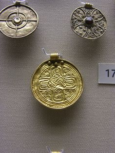 The British Museum Cabinet 38; 'The Coming of Christianity'. Photographs courtesy of Lindsay Kerr. Gold and garnet pendants with christian imagery based upon the cross. From 7thC Anglo-Saxon cemeteries, Kent. Wulfheodenas Facebook.