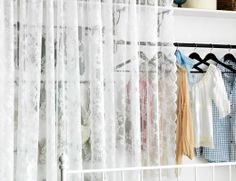 Clothes storage hidden behind ALVINE SPETS pair of lace curtains