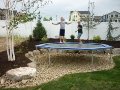 mulch and plants and rocks for the trampoline