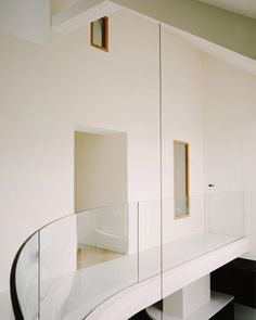 """A curving, white-concrete mezzanine that bridges across the living and dining area is described by Lesnoff-Rocard as """"a stratus, a low cloud passing quietly above your head"""". Clad Home, Timber Staircase, Paris Home, Oak Dining Table, Dining Area, London Apartment, White Concrete, Courtyard House, Architect House"""