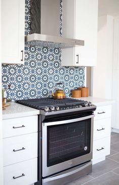 Riad Tile cement tile backsplash, slide in stainless steel range, gray cement style floors, white shaker cabinet, bronze cabinet pullsWhite kitchen with blue cement tile