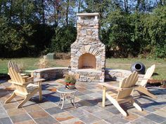 Whether for the mountains or lakeside, slate and stones combine to personalize this outdoor fireplace setting, Adirondacks were selected to create an area for conversation or simply relaxation outdoors.