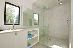 """This mirror slides on a track.  When mirror is """"in use"""" at the sink, it reveals a medicine cabinet behind.  When it isn't in use, the window takes its place.  Brilliant!   modern bathroom by Mueller Nicholls Cabinets and Construction"""