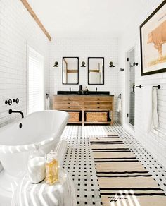 A vintage French burlap bathroom rug runner layers over vintage Carrara marble basketweave floor tiles in a cottage bathroom showcasing a roll top freestanding bathtub.