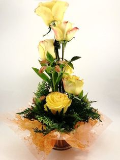 A tower of six beautiful yellow roses, surrounded by bundles of greens.