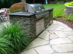 Outdoor Kitchen with Stacked Stone and Moss Rock Boulders