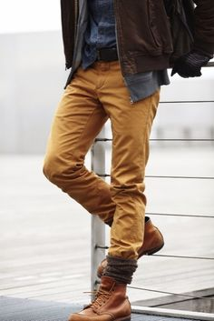 Choose a brown leather bomber jacket and mustard chinos for a comfortable outfit that's also put together nicely. Why not introduce brown leather boots to the mix for an added touch of style? Shop this look for $263: http://lookastic.com/men/looks/chinos-and-boots-and-socks-and-denim-shirt-and-bomber-jacket-and-hoodie-and-gloves/47 — Mustard Chinos — Brown Leather Boots — Brown Wool Socks — Navy Denim Shirt — Brown Leather Bomber Jacket — Grey Hoodie — Dark Brown Leather Gloves