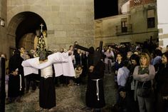 A man attached to a cross prays. This is a depiction of the final hours of Jesus Christ during the Holy Week procession of the 'Empalaos' in Valverde de la Vera. Empalaos make the steps of the 'Via Crucis while bound by rope to a crucifix as an act of penance and to honor a promise made to the Empalaos Brotherhood and the Christ of Vera Cruz. The process of dressing the Empalao in the traditional costume is taken with great care.