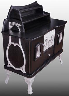 Upcycling-Kommode aus schwarz gebeiztem und gewachsten Holz mit weiß lackiereten Gusseisenelementen.