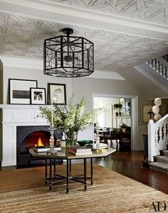 A custom-made Jasper light fixture hangs in the entrance hall of Net-a-Porter executive chairman Natalie Massenet's London home, which was decorated by Michael S. Smith; the vintage Karl Springer table is from Liz O'Brien, and the carpet is by Kravet | archdigest.com